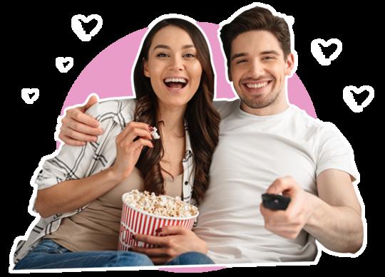 Frau und Mann lachend mit Popcorn beim Fernsehen