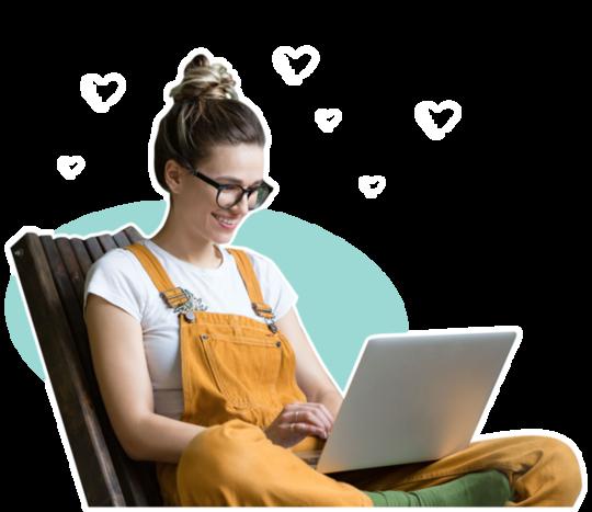 Junge Frau arbeitet fröhlich am Laptop